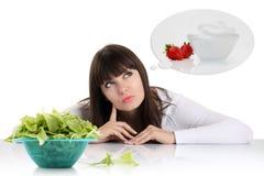 节食,少妇选择在果子之间的和甜点。衡量los 免版税库存照片