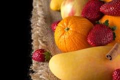 芒果、桔子、苹果和草莓在黄麻布料在b 免版税图库摄影