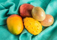 芒果、西番莲果和kiwano瓜在一块绿色布料 图库摄影