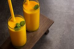 芒果与在头顶上秸杆的Lassi Smooothie汁液观看 免版税库存照片
