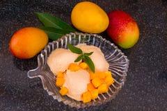 芒果与新芒果切片的冰淇凌与叶子在一块玻璃板铸造 免版税图库摄影