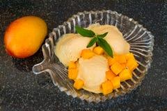 芒果与新芒果切片的冰淇凌与叶子在一块玻璃板铸造 库存照片