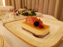 芒果乳酪蛋糕用在盘的草莓 免版税库存照片
