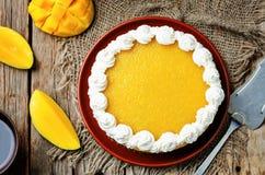 芒果乳酪蛋糕装饰用被鞭打的奶油和芒果纯汁浓汤 免版税图库摄影