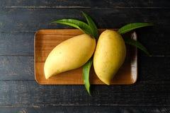 芒果和叶子在木盘子在木桌上 免版税库存图片