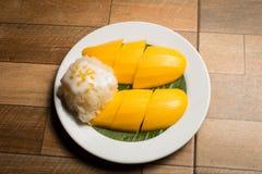 芒果和黏米饭在白色盘在木地板,泰国点心上普遍在泰国的夏天 免版税库存图片