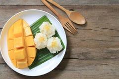 芒果和黏米饭在白色盘在棕色木地板和ha上 免版税库存图片