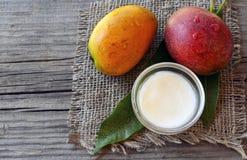芒果在一个玻璃碗的身体黄油和新鲜的成熟有机芒果结果实和在老木背景的叶子 免版税图库摄影