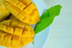 芒果成熟与恰好被削减的片断和叶子在板材 库存照片