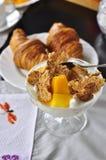 芒果新月形面包和玉米片可口早餐 免版税库存图片