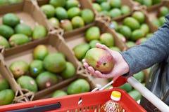 芒果果子在买家手上在杂货店 免版税库存图片