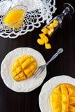 芒果果子立方体和芒果汁纯汁浓汤在黑暗的木背景 免版税库存照片