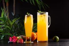 芒果柠檬水-在一个水罐的西番莲果和玻璃和果子在木背景 免版税库存照片