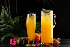 芒果柠檬水-在一个水罐的西番莲果和玻璃和果子在木背景 免版税库存图片