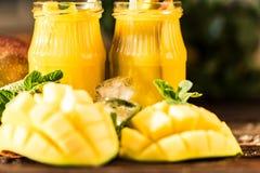 芒果汁和芒果在木桌上 库存图片
