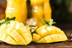 芒果汁和芒果在木桌上 库存照片