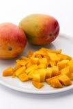 芒果立方体和两个整个芒果在一块白色板材 免版税图库摄影