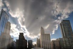 芝加哥与飞行在现代大厦的飞机的日落地平线 库存照片