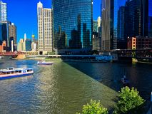 芝加哥河在一个五颜六色的夏天期间,当游览小船盖水,当游人和通勤者运用riverwalk时 免版税库存照片