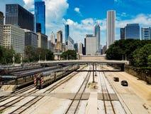 芝加哥,伊利诺伊,美国 07 05 2018年 与火车的芝加哥风景在一条铁路和汽车在一条路在前面 库存图片