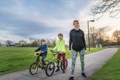 芝加哥, IL,美国, 2017年4月16日:有她的两个孩子的母亲在自行车在公园,为仅社论使用 免版税库存图片