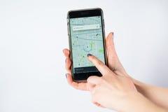芝加哥, IL,美国, 2月12,2017,妇女递拿着有一个开放Uber地图地点的一个智能手机在屏幕上为仅社论使用 免版税图库摄影
