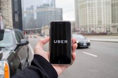 芝加哥, IL,美国, 2月21,2017,拿着有开放Uber的app的人一个智能手机在城市为仅社论使用 库存照片
