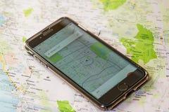 芝加哥, IL,美国, 2月12,2017,有一个开放Uber地图地点的智能手机在屏幕和一张地图上为仅社论使用 免版税库存图片