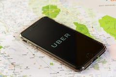 芝加哥, IL,美国, 2月12,2017,有一种Uber应用的智能手机在屏幕和一张地图上为仅社论使用 库存照片