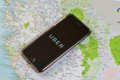 芝加哥, IL,美国, 2月12,2017,有一种Uber应用的智能手机在屏幕和一张地图上为仅社论使用 免版税库存照片