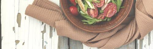 芝麻菜可口沙拉特写镜头用西红柿和在黏土的鸡胸脯在一张木桌,顶视图上滚保龄球 库存照片