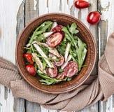 芝麻菜可口沙拉特写镜头用西红柿和在黏土的鸡胸脯在一张木桌,顶视图上滚保龄球 免版税库存照片