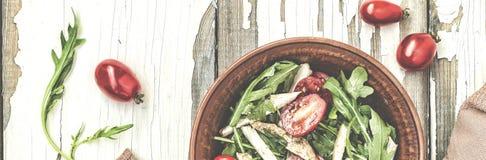 芝麻菜可口沙拉特写镜头用西红柿和在黏土的鸡胸脯在一张木桌,顶视图上滚保龄球 库存图片