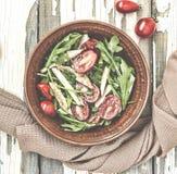 芝麻菜可口沙拉特写镜头用西红柿和在黏土的鸡胸脯在一张木桌,顶视图上滚保龄球 免版税图库摄影