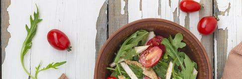 芝麻菜可口沙拉特写镜头用西红柿和在黏土的鸡胸脯在一张木桌,顶视图上滚保龄球 图库摄影