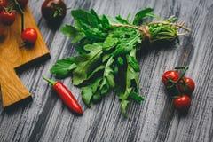 芝麻菜和辣椒在灰色背景 免版税库存图片