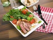 芝麻菜牛肉图油煎了沙拉蕃茄 库存照片