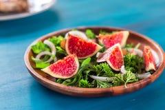 芝麻菜,在一块棕色陶器板材的无花果秋天沙拉在蓝色背景 顶视图 免版税库存图片