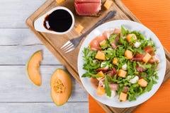 芝麻菜、熏火腿、无盐干酪和瓜沙拉,顶视图 免版税库存照片