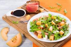 芝麻菜、熏火腿、无盐干酪和瓜沙拉,顶视图 免版税库存图片
