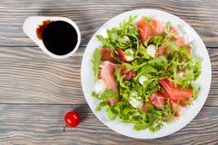 芝麻菜,熏火腿,在一个白色盘的无盐干酪沙拉 免版税库存照片