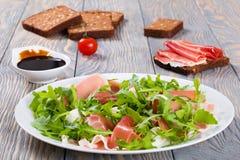 芝麻菜,熏火腿,在一个白色盘的无盐干酪沙拉 免版税库存图片