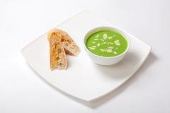 芦笋汤纯汁浓汤  在白色碗的芦笋奶油色汤有切片的白面包 免版税库存图片