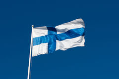 芬兰的旗子在蓝天前的。 免版税库存照片