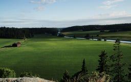 芬兰通过跑乡下、的河,绿色植被和谷仓 库存图片