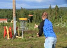 芬兰, Savonia :投掷入目标篮子的圆盘高尔夫球运动员 库存图片