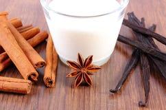 芬芳香草、肉桂条、八角和杯木表面上的牛奶 免版税库存图片