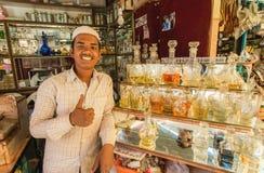 芬芳水和香水的年轻卖主在印度城市内部一家小商店  免版税库存图片