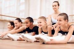芭蕾学校帮助年轻芭蕾舞女演员的教练员执行不同的编舞锻炼 免版税图库摄影