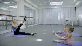 芭蕾舞团首席女演员怎么教两个孩子对strench在大明亮的健身房的腿 股票视频